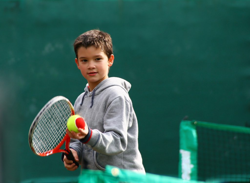Boy preparing to serve red ball with racquet