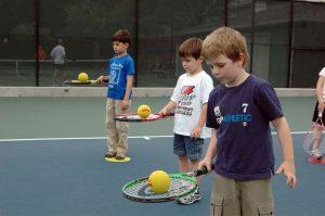 three boys balancing foam balls on tennis racquets